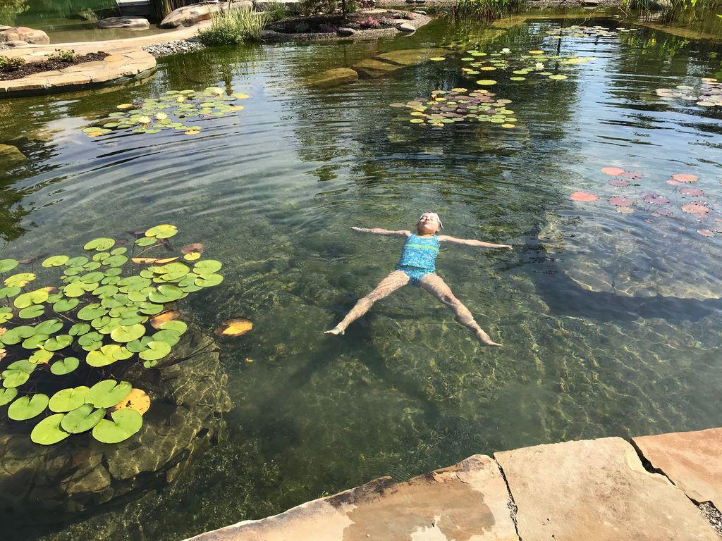 Girl enjoying a dip in a natural pool environment