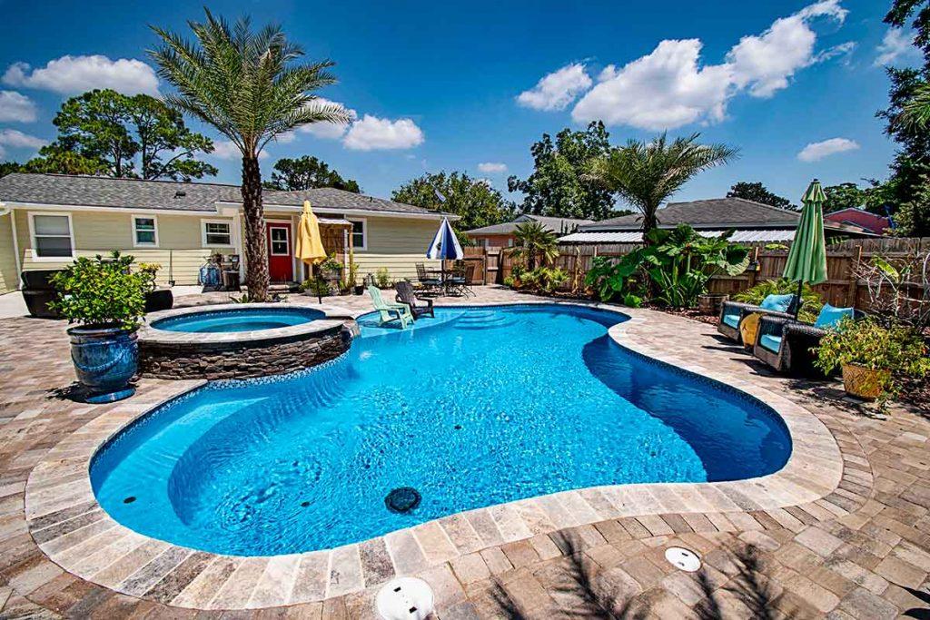 Designer pool - freeform pool design with travertine coping.