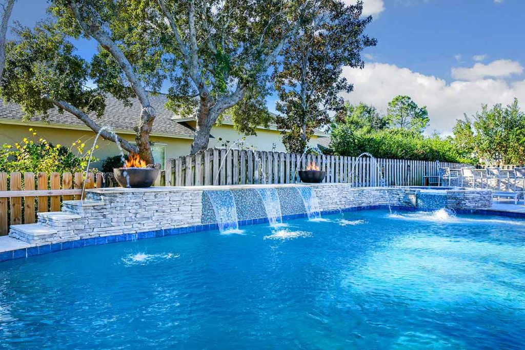 Fire and water features in pool designs are popular. Sheer descents and laminar jets with spillover spa.