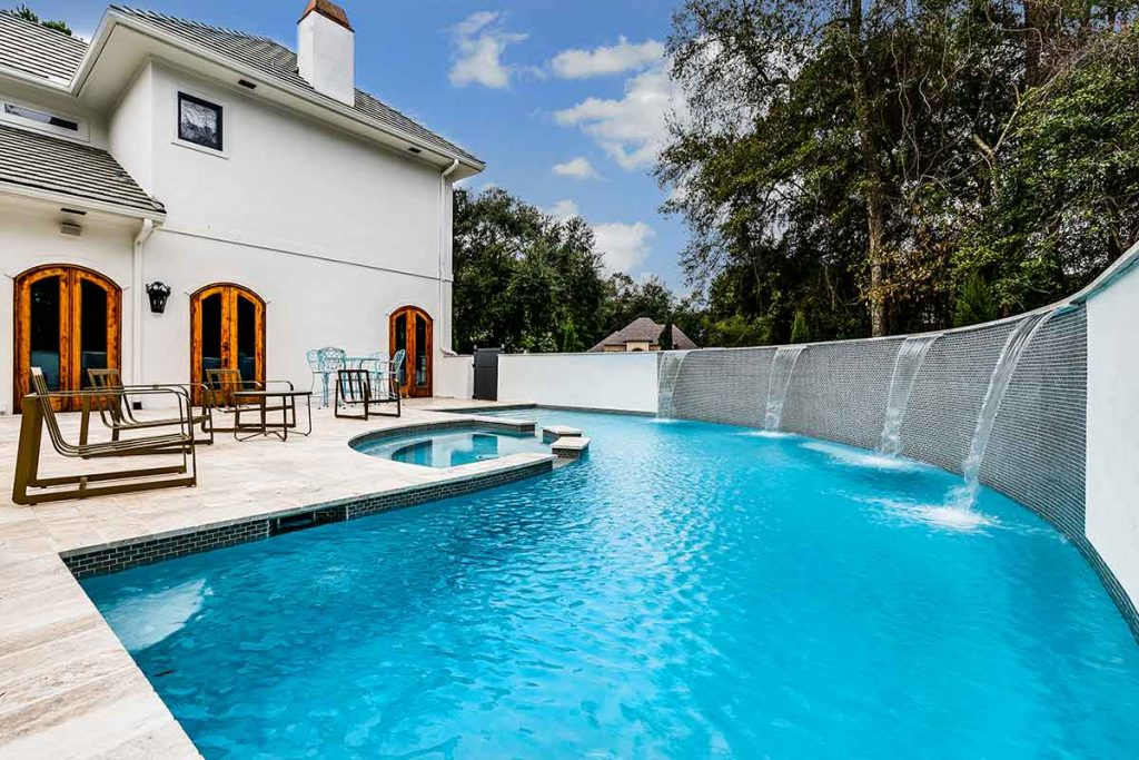 Modern pool design featuring multiple sheer descents from a huge retaining wall.
