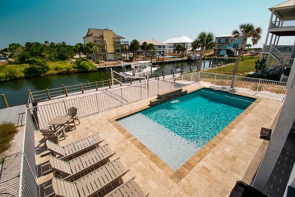 Luxury pool on waterfront property with easy access to guests dropping in for a dip.