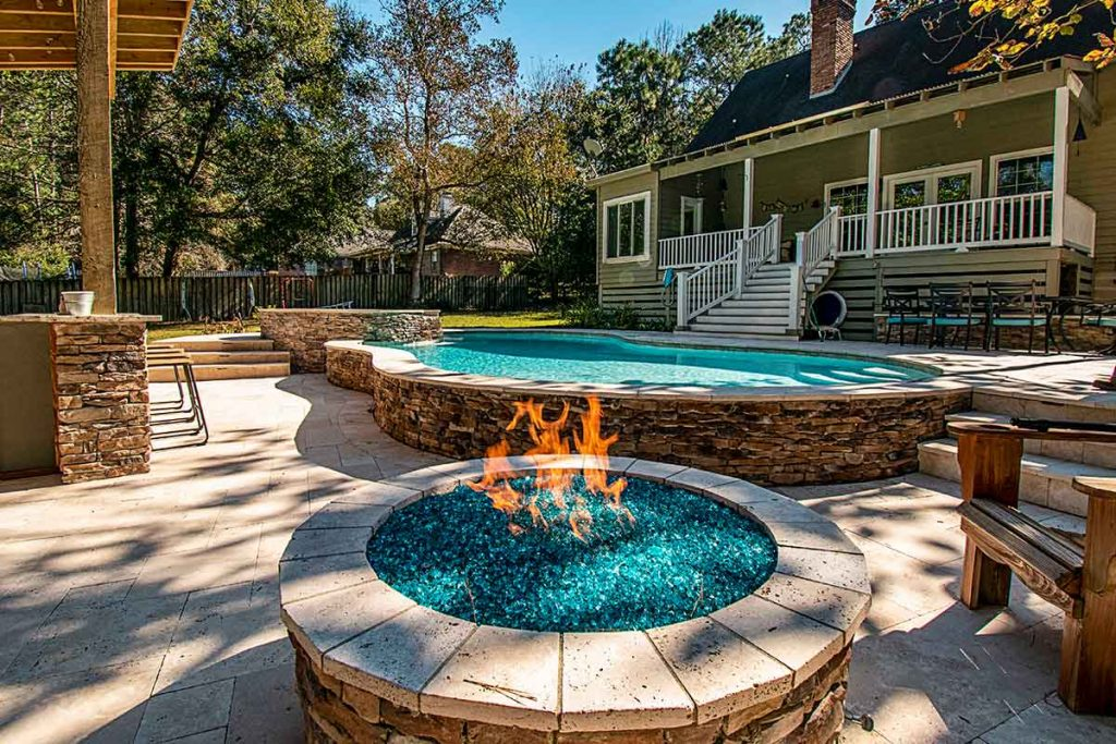 Firepit by the pool filled with crushed blue glass is the same color as the pool interior.