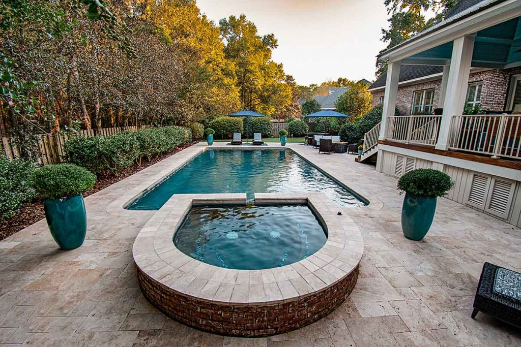 Making the most out of travertine decking by incorporating it into a raised detched spa.